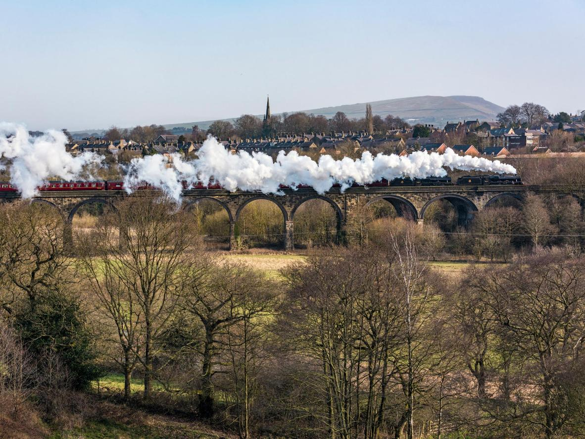 A steam train powers across New Mills Viaduct in Derbyshire