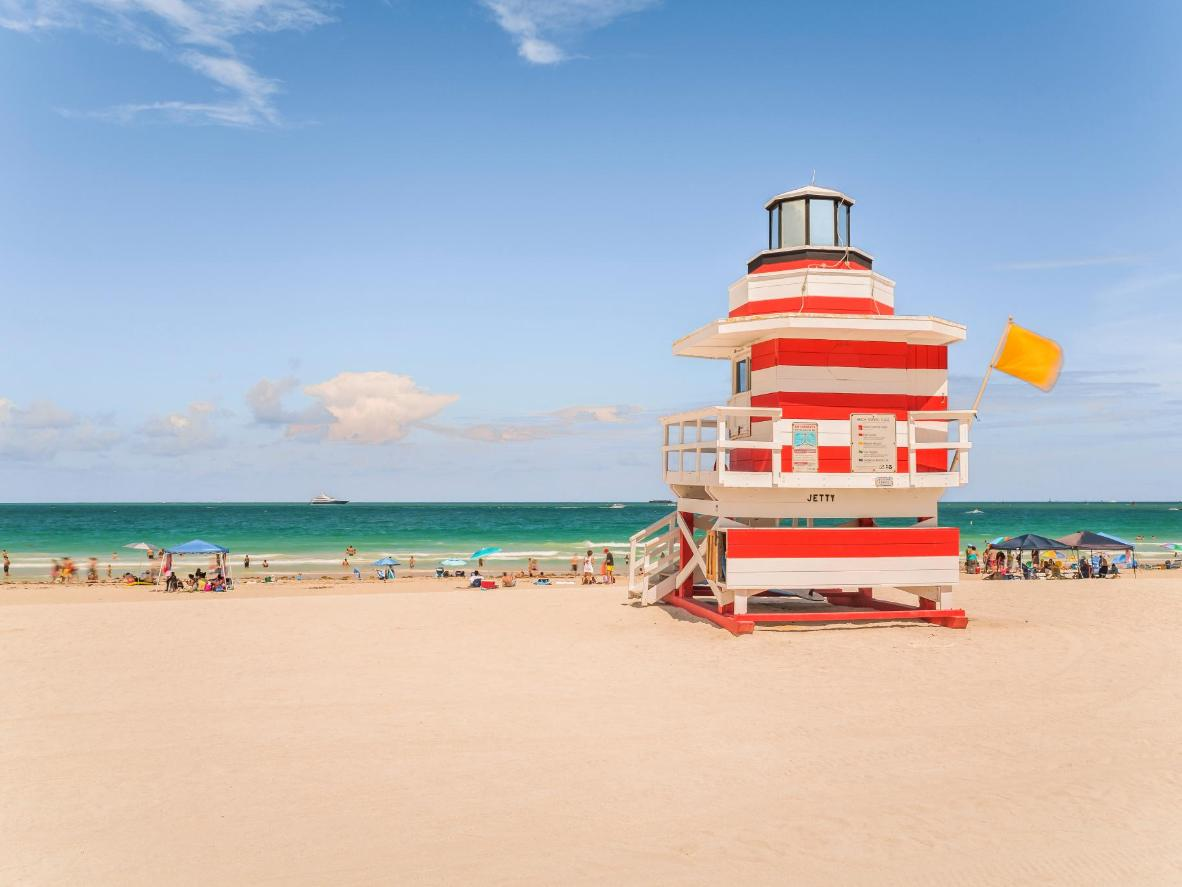 Sunbathe beside a classic striped lifeguard tower on Miami's 'SoBe'