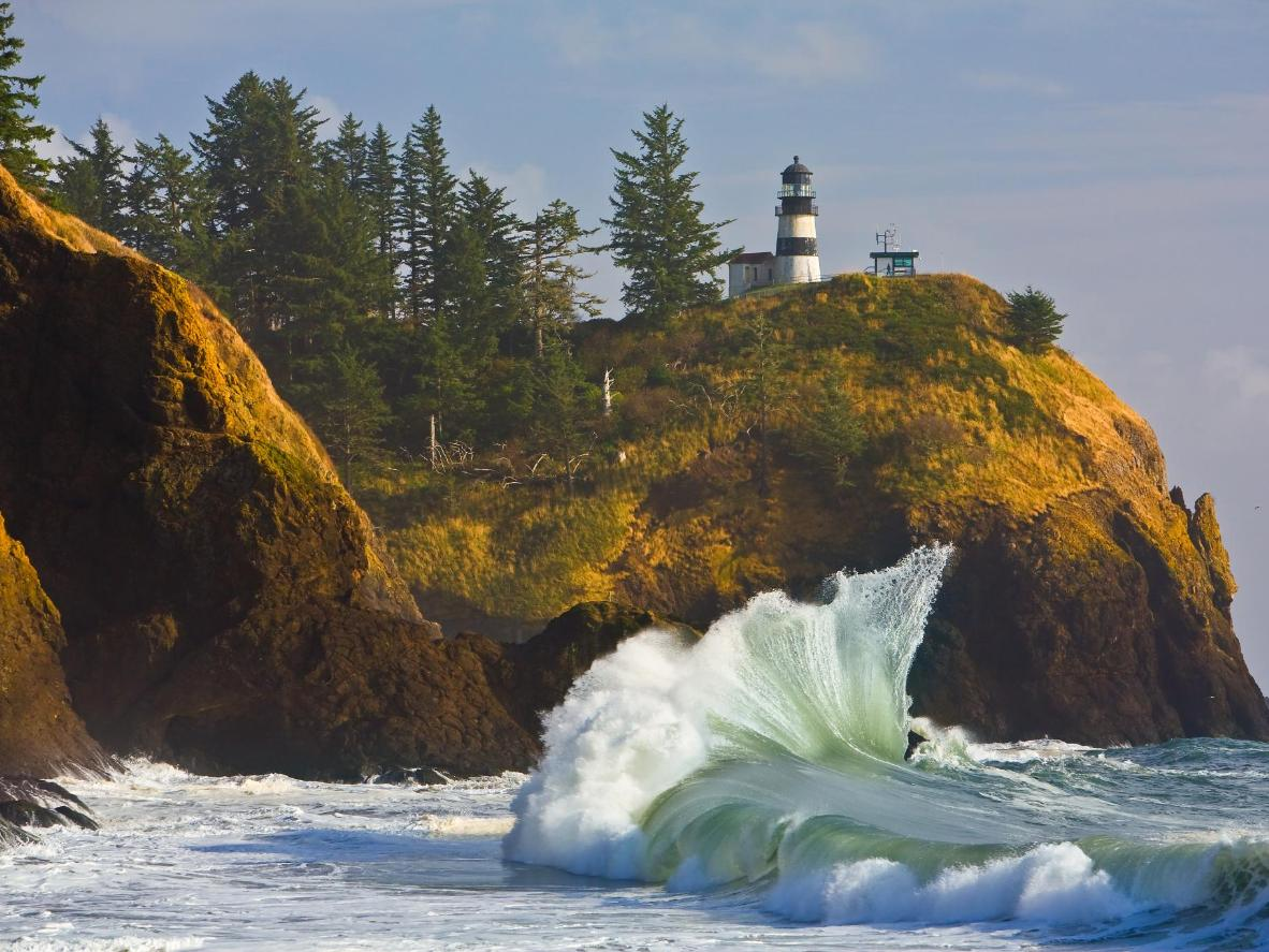 The lighthouse at Cape Disappointment towering over Pacific waves below