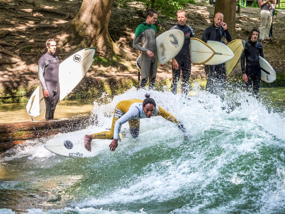 Surfers try their luck on the standing wave of the Eisbach