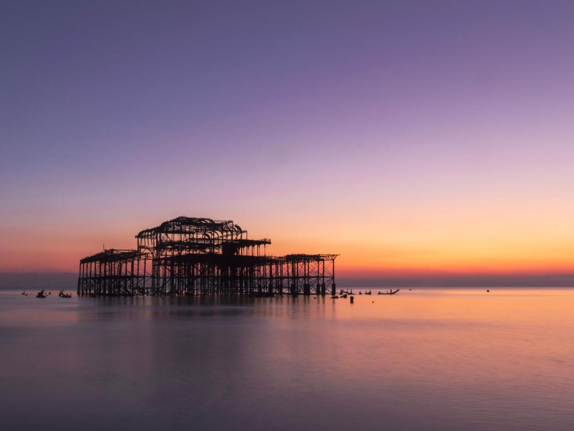 Watch the sunset behind the ruined West Pier